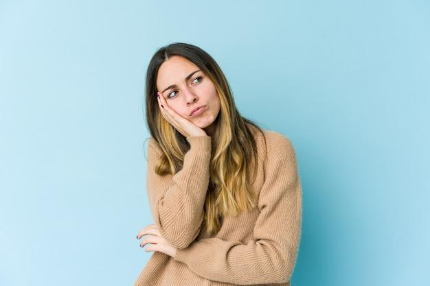 Jonge kaukasische vrouw die op blauwe muur wordt geïsoleerd die verveeld, vermoeid is en een ontspannende dag nodig heeft.