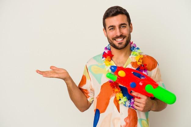Jonge kaukasische vrouw die op een hawaiiaanse partij een waterpistool houdt dat op witte achtergrond wordt geïsoleerd die een exemplaarruimte op een palm toont en een andere hand op taille houdt.