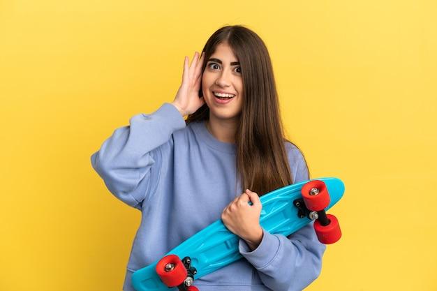 Jonge kaukasische vrouw die op gele achtergrond met een schaats wordt geïsoleerd en verrassingsgebaar doet