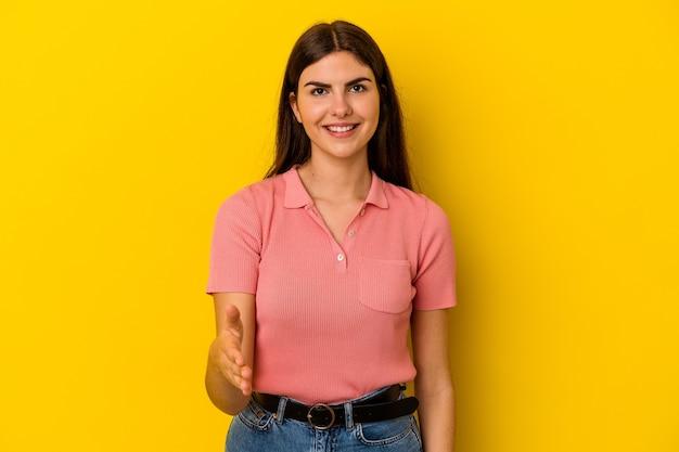 Jonge kaukasische vrouw die op gele achtergrond wordt geïsoleerd die hand bij camera in groetgebaar uitrekt.
