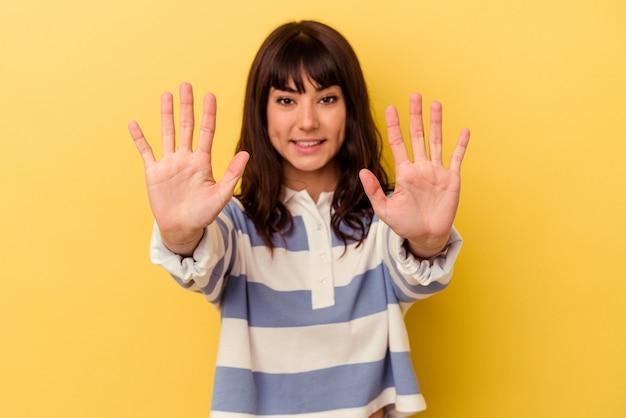 Jonge kaukasische vrouw die op gele achtergrond wordt geïsoleerd die nummer tien met handen toont.