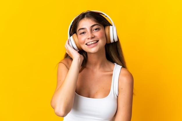 Jonge kaukasische vrouw die op gele het luisteren muziek wordt geïsoleerd