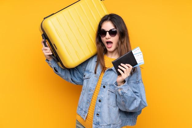 Jonge kaukasische vrouw die op gele muur in vakantie met koffer en paspoort wordt geïsoleerd en verrast