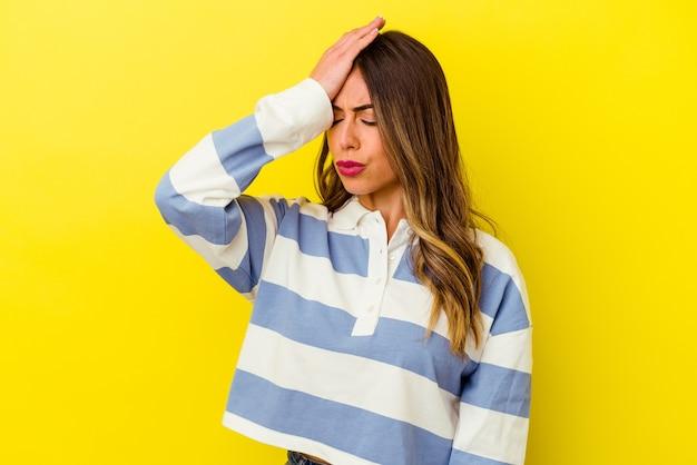 Jonge kaukasische vrouw die op gele muur wordt geïsoleerd die iets vergeet, voorhoofd met handpalm slaat en ogen sluit.