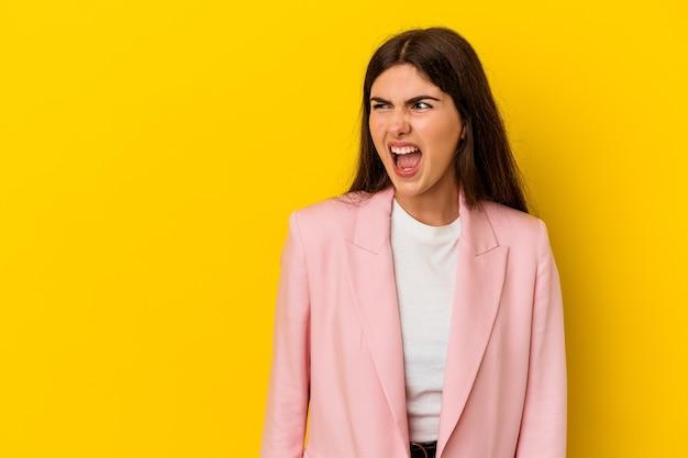 Jonge kaukasische vrouw die op gele muur wordt geïsoleerd die zeer boos, gefrustreerd woedeconcept schreeuwt.