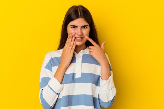 Jonge kaukasische vrouw die op gele muur wordt geïsoleerd met een sterke tandenpijn, kiespijn.