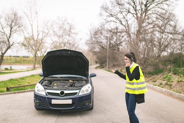 Jonge kaukasische vrouw, die op haar celtelefoon spreekt terwijl haar auto opgesplitst wordt op het wegauto en hulp bij pech onderweg.