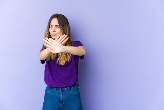 Jonge kaukasische vrouw die op purpere achtergrond wordt geïsoleerd die zich met uitgestrekte hand bevindt die stopbord toont, dat u verhindert.