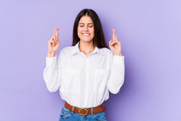 Jonge kaukasische vrouw die op purpere muur vingers kruisen voor het hebben van geluk