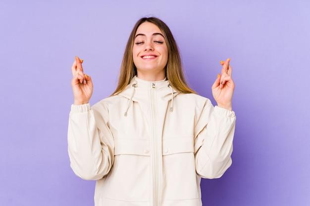 Jonge kaukasische vrouw die op purpere muur vingers kruist