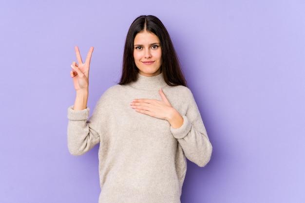 Jonge kaukasische vrouw die op purpere muur wordt geïsoleerd die een eed aflegt, die hand op borst zet.