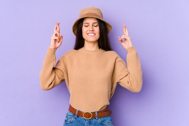 Jonge kaukasische vrouw die op purpere muur wordt geïsoleerd die vingers kruist voor het hebben van geluk