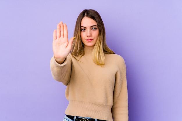 Jonge kaukasische vrouw die op purpere muur wordt geïsoleerd die zich met uitgestrekte hand bevindt die eindeteken toont, dat u verhindert.
