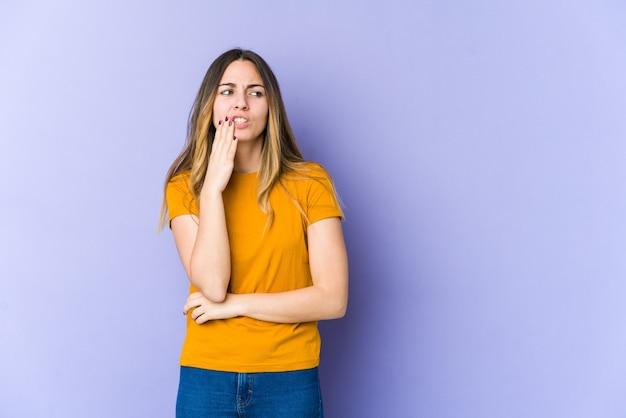 Jonge kaukasische vrouw die op purpere muur wordt geïsoleerd met een sterke tandenpijn, kiespijn.