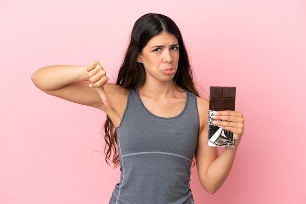 Jonge kaukasische vrouw die op roze achtergrond een chocoladetablet neemt die slecht signaal maakt