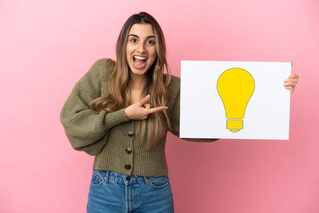Jonge kaukasische vrouw die op roze achtergrond een plakkaat met bolpictogram houdt en het richt