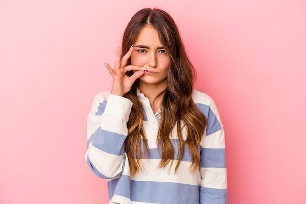 Jonge kaukasische vrouw die op roze achtergrond met vingers op lippen wordt geïsoleerd die een geheim houden.