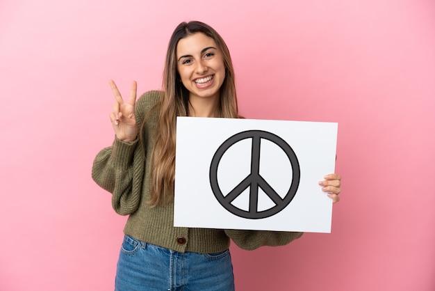 Jonge kaukasische vrouw die op roze achtergrond wordt geïsoleerd die een aanplakbiljet met vredessymbool houdt en een overwinning viert