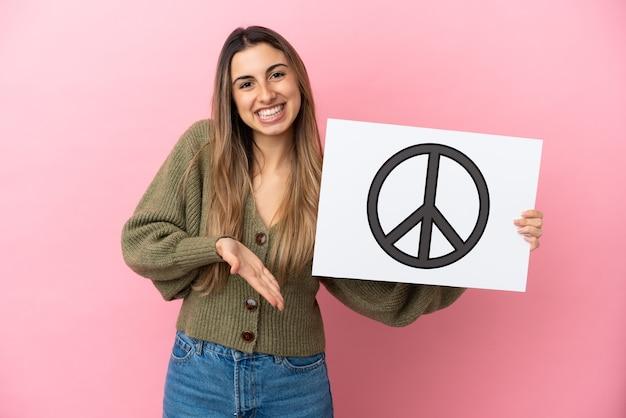 Jonge kaukasische vrouw die op roze achtergrond wordt geïsoleerd die een aanplakbiljet met vredessymbool houdt en het richt