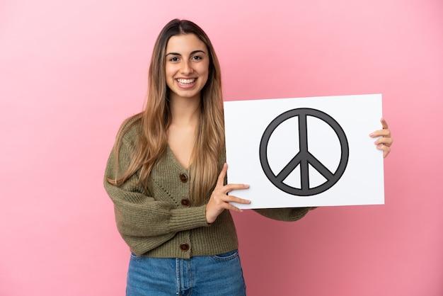 Jonge kaukasische vrouw die op roze achtergrond wordt geïsoleerd die een aanplakbiljet met vredessymbool met gelukkige uitdrukking houdt