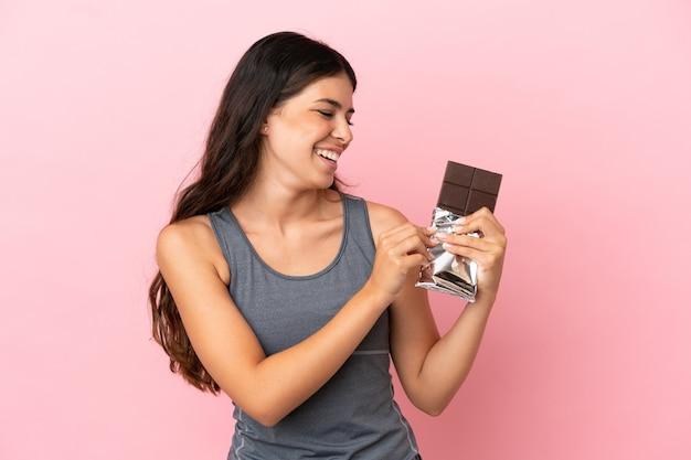 Jonge kaukasische vrouw die op roze achtergrond wordt geïsoleerd die een chocoladetablet neemt en happy