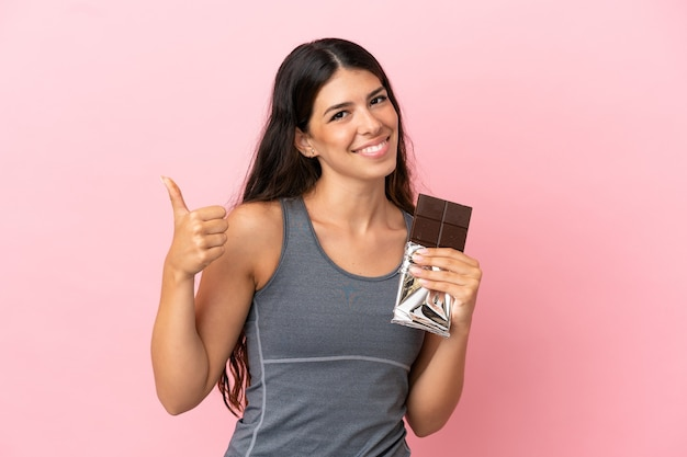 Jonge kaukasische vrouw die op roze achtergrond wordt geïsoleerd die een chocoladetablet neemt en met duim omhoog