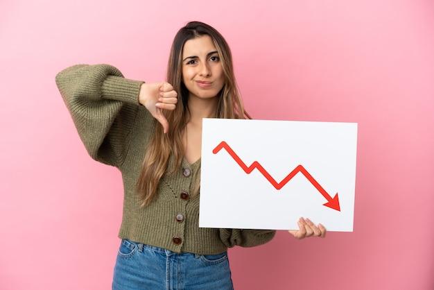 Jonge kaukasische vrouw die op roze achtergrond wordt geïsoleerd die een teken met een dalend symbool van de statistiekenpijl houdt en slecht signaal doet
