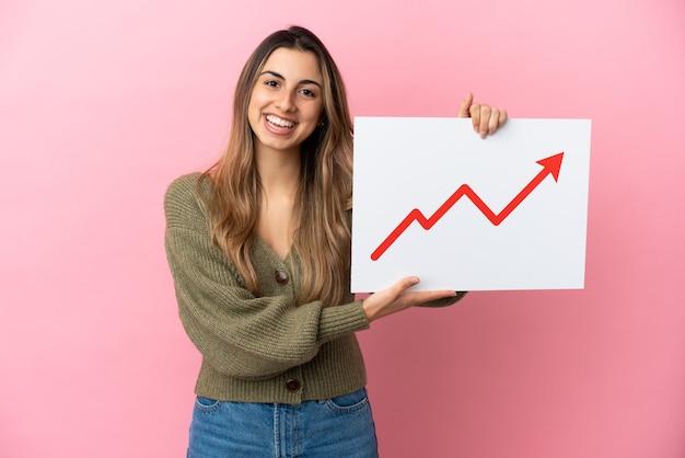 Jonge kaukasische vrouw die op roze achtergrond wordt geïsoleerd die een teken met een groeiend symbool van de statistiekenpijl houdt