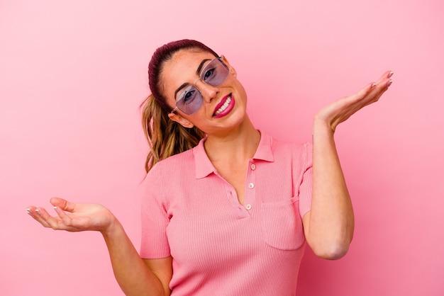 Jonge kaukasische vrouw die op roze achtergrond wordt geïsoleerd die met vinger naar u richt alsof uitnodigend kom dichterbij.