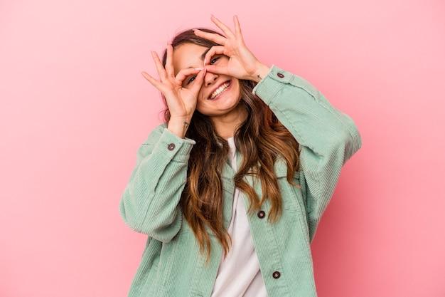 Jonge kaukasische vrouw die op roze achtergrond wordt geïsoleerd die ok teken over ogen toont