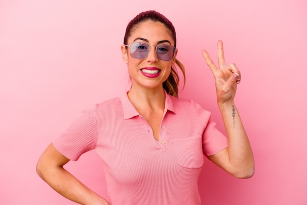 Jonge kaukasische vrouw die op roze achtergrond wordt geïsoleerd die overwinningsteken toont en breed glimlacht.