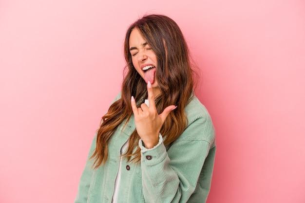 Jonge kaukasische vrouw die op roze achtergrond wordt geïsoleerd die rotsgebaar met vingers toont