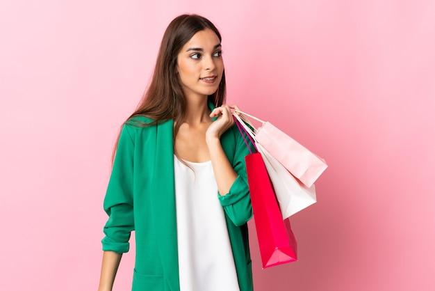 Jonge kaukasische vrouw die op roze boodschappentassen houdt en terugkijkt