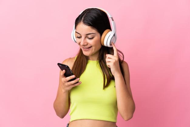 Jonge kaukasische vrouw die op roze het luisteren muziek met mobiel en het zingen wordt geïsoleerd