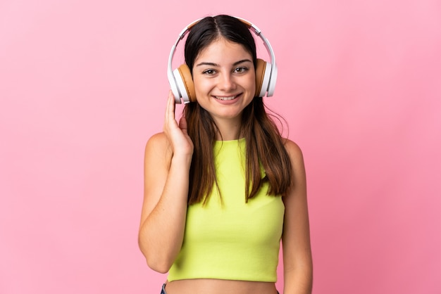 Jonge kaukasische vrouw die op roze het luisteren muziek wordt geïsoleerd