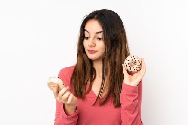 Jonge kaukasische vrouw die op roze holding donuts wordt geïsoleerd met gelukkige uitdrukking