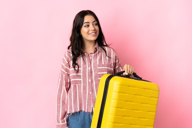 Jonge kaukasische vrouw die op roze muur in vakantie met reiskoffer wordt geïsoleerd