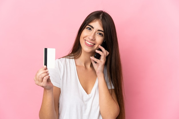 Jonge kaukasische vrouw die op roze muur wordt geïsoleerd die een gesprek met de mobiele telefoon houdt en een creditcard houdt
