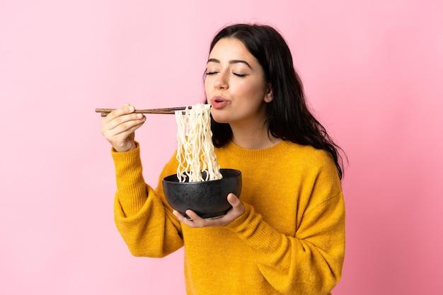 Jonge kaukasische vrouw die op roze muur wordt geïsoleerd die een kom noedels met eetstokjezand houdt dat het blaast omdat zij heet zijn