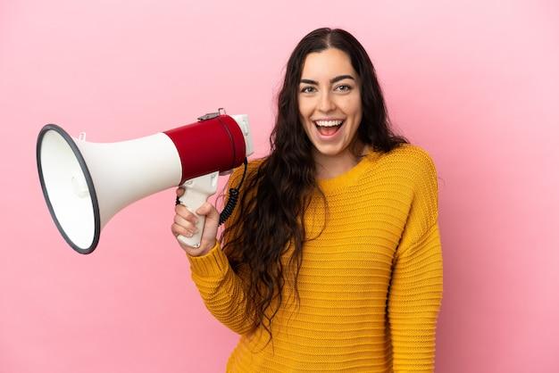 Jonge kaukasische vrouw die op roze muur wordt geïsoleerd die een megafoon houdt en met verrassingsuitdrukking