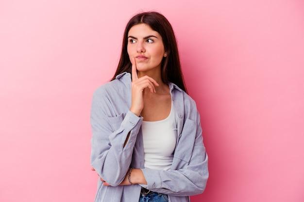 Jonge kaukasische vrouw die op roze muur wordt geïsoleerd die, een strategie plant, nadenkt over de manier van een bedrijf