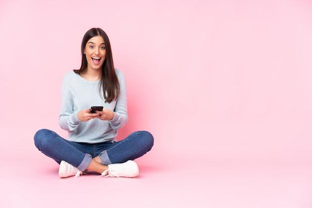 Jonge kaukasische vrouw die op roze muur wordt verrast die en een bericht verzendt