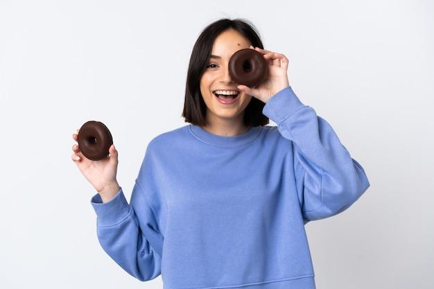 Jonge kaukasische vrouw die op wit wordt geïsoleerd dat een doughnut houdt en gelukkig