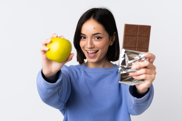 Jonge kaukasische vrouw die op witte achtergrond wordt geïsoleerd die een chocoladetablet in de ene hand en een appel in de andere neemt