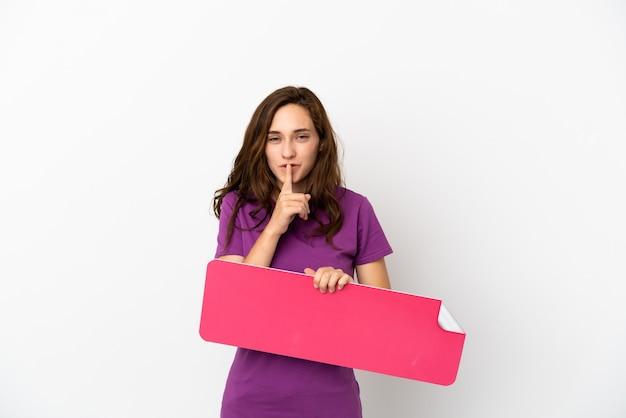 Jonge kaukasische vrouw die op witte achtergrond wordt geïsoleerd die een leeg plakkaat houdt die stiltegebaar doet