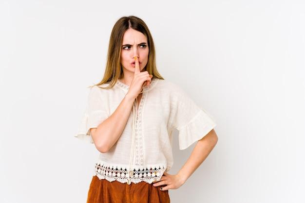 Jonge kaukasische vrouw die op witte muur wordt geïsoleerd die een geheim houdt of om stilte vraagt.