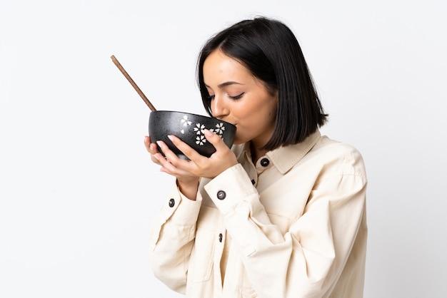 Jonge kaukasische vrouw die op witte muur wordt geïsoleerd die een kom noedels met eetstokjes houdt en het eet