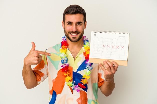 Jonge kaukasische vrouw die op zijn vakanties wacht die een kalender houden die op witte achtergrondpersoon wordt geïsoleerd die met de hand wijst naar een overhemdskopieerruimte, trots en zeker