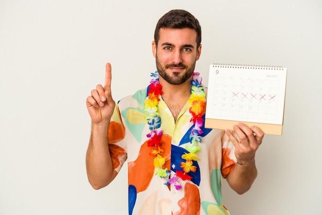 Jonge kaukasische vrouw die op zijn vakanties wacht die een kalender houden die op witte muur wordt geïsoleerd die nummer één met vinger toont
