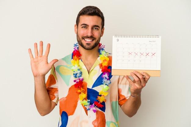 Jonge kaukasische vrouw die op zijn vakanties wacht die een kalender houden die op witte muur wordt geïsoleerd die vrolijk toont nummer vijf met vingers toont.